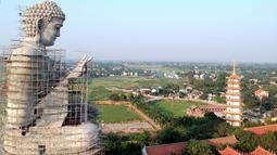 Foto udara pada 18 Mei 2019 memperlihatkan patung Buddha raksasa yang sedang dibangun di pagoda Khai Nguyen di distrik Son Tay, pinggiran Hanoi. Pengerjaan patung Buddha setinggi 72 meter ini dimulai pada 2015 dan diperkirakan selesai dalam lima tahun mendatang. (Photo by Manan VATSYAYANA/AFP)