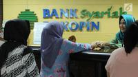 Nasabah melakukan transaksi di Bank Bukopin Syariah, Jakarta, Selasa (30/1). Data OJK yang terekam sampai Oktober 2017 mencatat, pertumbuhan aset perbankan syariah mencapai 19,79% secara tahunan menjadi Rp 395,89 triliun. (Liputan6.com/Angga Yuniar)