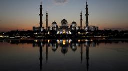 Matahari terbenam di belakang Masjid Agung Sheikh Zayed di Abu Dhabi, Uni Emirat Arab (8/11/2019). Masjid Agung Sheikh Zayed di bangun pada tahun 1996 dengan 82 kubah bergaya Maroko dan semuanya dihias dengan batu pualam putih. (AFP Photo/Kamran Jebreili)