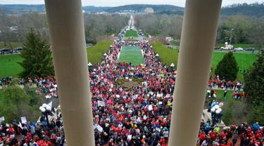Ribuan guru dari seluruh  Kentucky berkumpul di luar gedung DPR negara bagian saat menggelar aksi unjuk rasa di Frankfort, Amerika Serikat, Senin (2/4). Mereka turun ke jalan menuntut kenaikan gaji dan pendanaan bagi sekolah. (AP/Timothy D. Easley)
