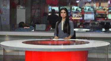 Pembawa berita transgender pertama di Pakistan,  Marvia Malik (21) membacakan berita untuk saluran televisi Kohenoor di Lahore, Selasa (27/3). Malik tampil perdana di televisi pada 23 Maret lalu dan langsung menjadi viral di media sosial. (ARIF ALI/AFP)