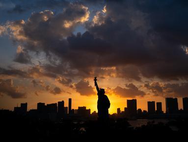 Replika Patung Liberty terlihat saat matahari terbenam di Odaiba, Tokyo, Jepang (29/7). Odaiba adalah sebuah pulau buatan di Teluk Tokyo, Jepang yang dihubungkan dengan pusat kota Tokyo dengan Jembatan Rainbow. (AFP Photo/Martin Bureau)