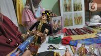 Ibu rumah tangga menyelesaikan pembuatan boneka adat Indonesia di Ammie Dolls di Komplek Pondok Tirta, Depok, Kamis (13/08/2020). Pada masa pandemi ini produksi dan penjualan anjlok hingga 95 persen menyebabkan perajin beralih ke bidang lain untuk mencukupi kebutuhan hidup. (merdeka.com/Arie Basuki)