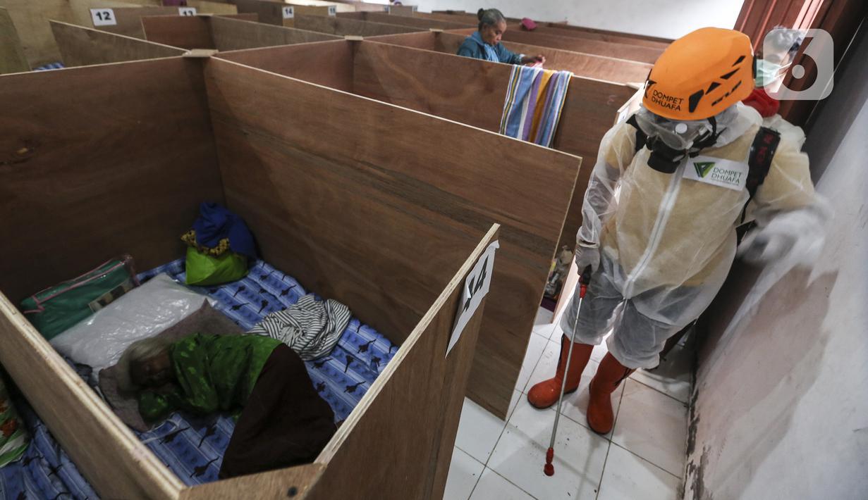 Relawan mendisinfeksi bilik pengungsi Gunung Merapi di Barak Pengungsian Glagaharjo, Cangkringan, Sleman, Yogyakarta, Jumat (20/11/2020). Penyemprotan yang dilakukan dua hari sekali ini untuk mencegah penularan COVID-19. (Liputan6.com/Johan Tallo)