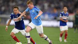 Gelandang Manchester City, Kevin De Bruyne, berusaha melewati striker Yokohama Marinos, Teruhito Nakagawa, pada laga pramusim di Stadion Yokohama, Jepang, Sabtu (27/7). Yokohama kalah 1-3 dari City. (AFP/Charly Triballeau)