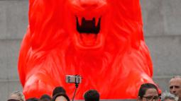 Sejumlah wanita berselfie di depan singa fluorescent merah di pangkalan Kolom Nelson di Trafalgar Square di London (19/9). Singa merah baru merupakan proyek seni yang diciptakan oleh perancang Es Devlin. (AP Photo/Frank Augstein)