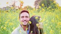 Hamish Daud dan Raisa Andriana berpose di antara bunga-bunga perkebunan Mustard di India. (Instagram/hamishdw)