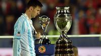 Lionel Messi, diantara trofi juara Copa America yang kembali gagal diraihnya. (AFP PHOTO/RODRIGO ARANGUA)