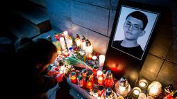 Seorang pria menyalakan lilin di depan foto Jan Kuciak di Bratislava (26/2). Pembunuhan itu terjadi di tengah pembuatan laporan investigatif Kuciak soal kasus dugaan kecurangan pajak yang melibatkan pengusaha. (AFP Photo/Vladimir Simicek)