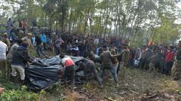 Polisi dan pekerja kehutanan bersama penduduk desa menutupi tubuh gajah betina dengan  plastik, yang sedang hamil, setelah kereta penumpang yang melaju menabrak dua gajah yang melintasi rel di desa Batasi dekat perbatasan India-Nepal, sekitar 37 km dari Siliguri (11/12/2019). (AFP/Diptendu Dutta)