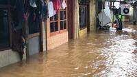 Warga beraktivitas di tengah banjir yang merendam kawasan Kebon Pala, Jakarta Timur, Selasa (25/2/2020). Akibat banjir yang tak kunjung surut, aktivitas warga di kawasan tersebut menjadi terganggu, terlebih dengan adanya pemadaman listrik. (Liputan6.com/Immanuel Antonius)