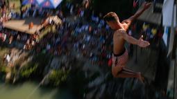 Seorang peserta melakukan terjun bebas dari jembatan Ura e Shejnt dalam kompetisi menyelam tradisional ke-68 di Gjakova, Kosovo, 22 Juli 2018. Kompetisi ini dilakukan dari ketinggian 22 meter. (AP/Visar Kryeziu)