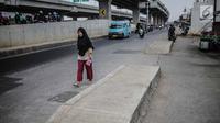 Pejalan kaki melintas di samping trotoar yang berada di tengah jalan di kawasan Kalimalang, Senin (16/9/2019). Selain dikeluhkan pengendara karena membahayakan, keberadaan trotoar tak lazim itu dinilai mempersempit jalan dan kerap menimbulkan macet saat jam sibuk. (Liputan6.com/Faizal Fanani)