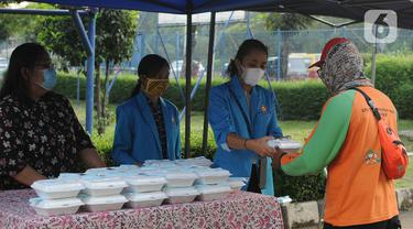 Sejumlah mahasiswa memberikan makanan gratis kepada masyarakat di Universitas Kristen Indonesia (UKI), Cawang, Jakarta, Selasa (16/3/2021). Kegiatan berbagi makanan gratis yang dilakukan oleh civitas akademi UKI itu diselenggarakan selama tiga bulan. (Liputan6.com/Herman Zakharia)