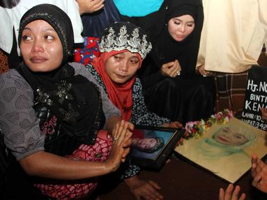 Keluarga dan sahabat saat mendoakan komedian Betawi Nur Sarinuri atau lebih dikenal Mpok Nori seusai dimakamkan di TPU Pondok Ranggon, Jakarta Timur, Jumat (3/4/2015). (Liputan6.com/Helmi Afandi)