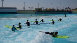 Peselancar mendapat instruksi di kolam ombak Wave Park di Siheung, Korea Selatan, 18 Oktober 2020. Korea Selatan memiliki kolam ombak terbesar di dunia dengan teknologi Wavegarden Cove yang memiliki beberapa modul produksi gelombang dan menjadi kolam gelombang dengan jumlah terbesar. (Ed JONES/AFP)