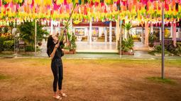 Seorang perempuan menggantung lampion di Wat Phra That Hariphunchai, Lamphun, Thailand, 1 November 2020. Sekitar 100.000 lampion digantung di Wat Phra That Hariphunchai sebagai bagian dari perayaan festival tradisional Yi Peng. (Xinhua/Zhang Keren)