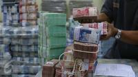 Petugas tengah mengepakan mata uang rupiah di kantor Cash BNI, Jakarta, Jumat (17/6). Kebutuhan uang tunai di ATM dan outlet diperkirakan mencapai lebih dari Rp 62 triliun, naik 8% dari realisasi tahun sebelumnya. (Liputan6.com/ Angga Yuniar)
