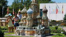 Pengunjung melihat miniatur Katedral Moskow Saint Basil di Taman Minimundus, Klagenfurt, Austria, Senin (8/8). Sekitar 150 model bangunan unik dari berbagai belahan dunia dipamerkan di Taman Minimundus. (REUTERS / Heinz-Peter Bader)