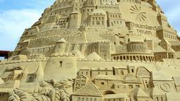 Seorang seniman saat membuat istana pasir di Landschaftspark di Duisburg, Jerman , (1/9). Seniman dari Duisburg burusaha meraih Guinness Book of World Records dengan membuat istana pasir tertinggi yang pernah ada. (Marcel Kusch / dpa via AP)