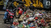 Pengendara motor membuang sampah di kolong tol Wiyoto Wiyono, Tanjung Priok, Jakarta, Selasa (5/11/2019). Sampah yang menumpuk  berasal dari sampah rumah tangga warga sekitar yang tidak memiliki tempat pembuangan sampah sementara.  (Liputan6.com/Faizal Fanani)