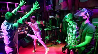 Band bermain untuk seorang pelanggan di bar kawasan hiburan Patpong, Bangkok, Thailand, Rabu (1/7/2020). Mulai 1 Juli, bar di Bangkok kembali diizinkan buka setelah pengurangan pembatasan untuk menghentikan penyebaran virus corona COVID-19. (Lillian SUWANRUMPHA/AFP)