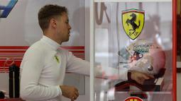 Pembalap Ferrari Sebastian Vettel dari Jerman bersiap di pit selama latihan bebas pertama di Sirkuit Internasional Bahrain Formula Satu di Sakhir, Bahrain, (5/4). F1 GP Bahrain akan berlangsung pada hari Minggu. (AP Photo/Luca Bruno)