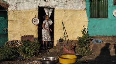 Seorang perempuan berdiri di depan pintu sebuah rumah di Kota Gondar, Ethiopia pada 09 November 2020. (Photo by EDUARDO SOTERAS / AFP)