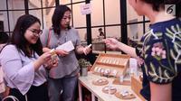 Pegunjung melihat booth start up di EV Hive @ Filateli di Pasar Baru Jakarta, Jumat (6/4). EV Hive @ Filateli adalah kerja sama antara EV Hive dan PT Pos Properti untuk mengaktivasi bangunan bersejarah dari PT Pos Properti. (Liputan6.com/Angga Yuniar)