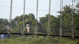 Warga asyik berswafoto di atas jembatan gantung, Kelurahan Curug, Bojongsari, Kota Depok, Jawa Barat, Senin (24/8/2020). Setiap sore, warga sekitar bermain di jembatan tersebut sambil menikmati matahari tenggelam. (merdeka.com/Dwi Narwoko)