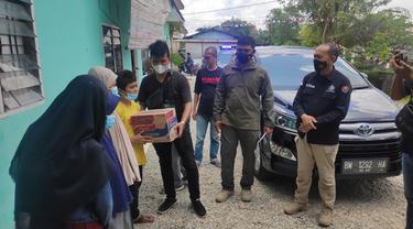 Wartawan membagikan mi instan dan sembako ke penghuni panti asuhan disaksikan Kabid Humas Polda Riau.
