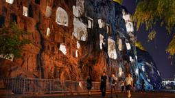 Sejumlah wisatawan mengunjungi Gua Longmen, sebuah lokasi wisata berpanorama menawan di Luoyang, Provinsi Henan, China tengah, pada 7 Juli 2020. Berbagai bentuk tur malam hari di Luoyang menarik banyak wisatawan dan mendongkrak perekonomian. (Xinhua/Li An)