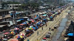 Warga memadati jalan yang dipenuhi lapak pedagang di area pasar tradisional selama karantina wilayah masih diberlakukan pemerintah setempat di Dhaka, Bangladesh (12/5/2020). (AFP/Munir Uz Zaman)