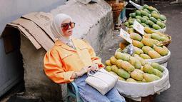 Pasar dengan deretan buah mangga menjadi salah satu lokasi pemotretan Tantri Namirah. Ibu satu anak ini tampil senada dengan blazer bewarna oren dan kacamata yang membuat penampilan semakin trendi. (Liputan6.com/IG/@tantrinamirah)