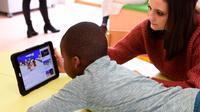 Seorang perawat bersama salah satu anak sedang menonton dari layar tablet di Rumah Sakit Ecole di Neuilly-Plaisance, dekat Paris, 21 Maret 2017. Rumah sakit yang khusus untuk anak penderita autis ini baru saja dibuka untuk umum. (BERTRAND GUAY/AFP)