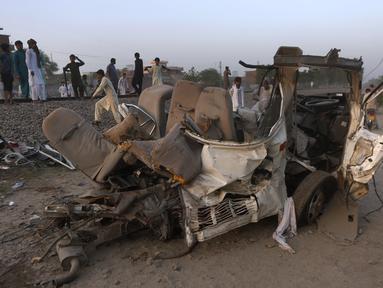 Warga berkumpul dekat puing-puing bus yang tertabrak kereta api di Farooq Abad, Distrik Sheikhupura, Pakistan, Jumat (3/7/2020). Kecelakaan tersebut mengakibatkan 22 orang tewas. (AP Photo/K.M. Chaudary)