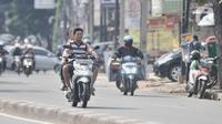 Pengendara sepeda motor tanpa mengenakan helm dan masker melintas di Jalan Pasar Minggu, Jakarta, Rabu (8/4/2020). Organisasi Kesehatan Dunia (WHO) telah merekomendasikan agar menggunakan masker saat berada di tempat umum demi memutus mata rantai penyebaran virus Corona. (merdeka.com/Iqbal Nugroho)
