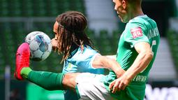Pemain Werder Bremen,  Ludwig Augustinsson, berebut bola dengan pemain Wolfsburg, Kevin Mbabu, pada laga Bundesliga di Weserstadion Minggu (7/6/2020). Werder Bremen takluk 0-1 dari Wolfsburg. (AFP/Patrik Stollarz)