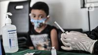 Petugas paramedis menyiapkan peralatan imunisasi saat program BIAS di Kantor Kelurahan Tamansari, Jakarta, Selasa (24/11/2020). Selama masa pandemi, pemerintah melalui Dinas Kesehatan tetap menggelar Bulan Imunisasi Anak Sekolah (BIAS). (merdeka.com/Iqbal S. Nugroho)
