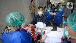 Petugas Kelompok Penyelenggara Pemungutan Suara (KPPS) menjalani rapid test Covid-19 di kantor Kelurahan Pondok Benda, Tangerang Selatan, Jumat (27/11/2020). Rapid Test tersebut diikuti 1.017 anggota KPPS serta Petugas Pengamanan Tempat Pemungutan Suara (PAM TPS). (merdeka.com/Dwi Narwoko)