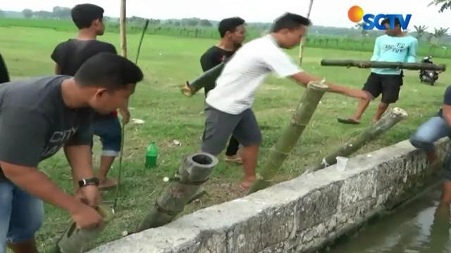 Warga Desa Kedal Rejo, Kabupaten Tuban, Jawa Timur, menunggu buka puasa dengan bermain Ke-ke-an meriam bambu.