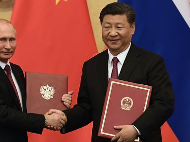 Presiden Rusia Vladimir Putin (kiri) bersalaman dengan Presiden China Xi Jinping saat upacara penandatanganan kerja sama di Beijing, China (8/6). Untuk kali ke-25 Presiden Rusia Vladimir Putin bertemu dengan Presiden Xi Jinping. (AFP/Pool/Nicolas Asfouri)