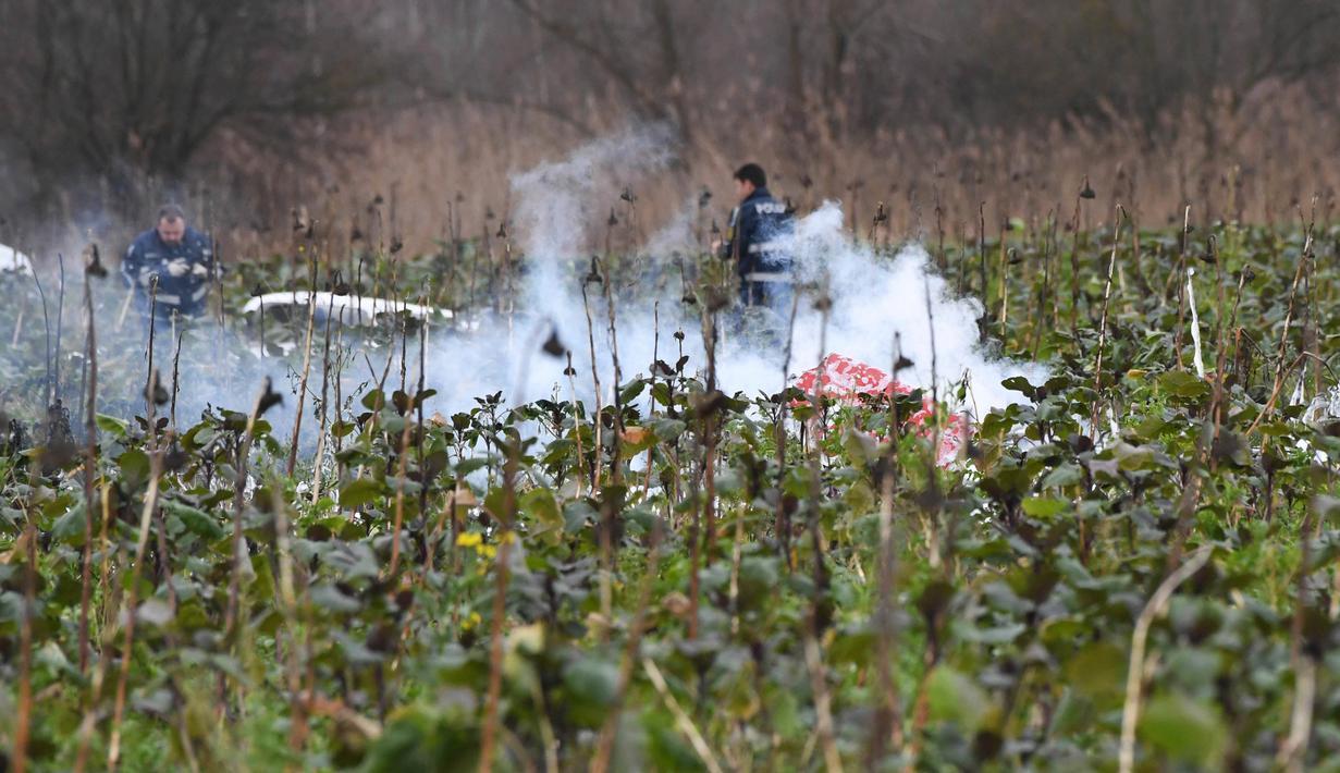 Petugas pemadam kebakaran memeriksa lokasi terjadinya kecelakaan udara antara pesawat kecil dengan helikopter di kota Philippsburg, Jerman, Selasa (23/1). Empat orang dilaporkan menjadi korban tewas tabrakan di udara tersebut. (Uli Deck/dpa via AP)