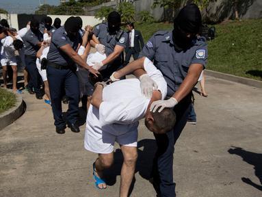 Petugas kepolisian menggelandang anggota geng Mara Salvatrucha di Zacatecoluca, El Salvador (31/1). 32 anggota geng tersebut dituduh membunuh pasukan keamanan dalam beberapa bulan terakhir. (AP Photo/Moises Castillo)