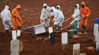 Petugas mengubur peti jenazah berisi korban virus corona COVID-19 ke sebuah pemakaman di Jakarta, Rabu (15/4/2020). Hingga sore ini, jumlah kasus COVID-19 di Indonesia sebanyak 5.136 positif, 446 sembuh, dan 469 meninggal dunia. (Bay ISMOYO/AFP)