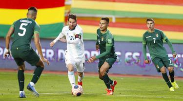 Striker Argentina, Lionel Messi, berusaha melewati pemain Bolivia pada laga kualifikasi Piala Dunia 2022 di Estadio Hernando Siles, Rabu (14/10/2020). Argentina menang dengan skor 2-1. (AP/Juan Karita)