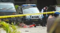 Polisi memeriksa jenazah seorang yang diduga sebagai pelaku bom bunuh diri di Mapolrestabes Medan, Sumatera Utara, Rabu (13/11/2019). Satu orang terduga pelaku bom bunuh diri tewas di lokasi kejadian. (ATAR/AFP)