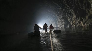 Sejumlah warga menyusuri terowongan saat akan memperbaiki sistem air yang mereka buat di Caracas, Venezuela, Kamis (11/6/2020). Tanpa air minum dari otoritas pemerintah, penduduk Esperanza mengumpulkan air dari dalam terowongan jalan raya Baralt yang tidak pernah selesai. (AP Photo/Matias Delacroix)