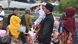 Seorang anak berambut gimbal digendong saat akan melakukan ruwatan atau pemotongan rambut gimbal di komplek candi Arjuna, Dieng, Jateng, Minggu (3/7). Acara ini dilaksanakan pada 5-7 Agustus 2016. (Gholib)