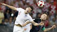 Gelandang Kroasia, Ivan Rakitic, duel udara dengan bek Inggris, John Stones, pada laga semifinal Piala Dunia di Stadion Luzhniki, Rabu (11/7/2018). Kroasia menang 2-1 atas Inggris. (AP/Rebecca Blackwell)